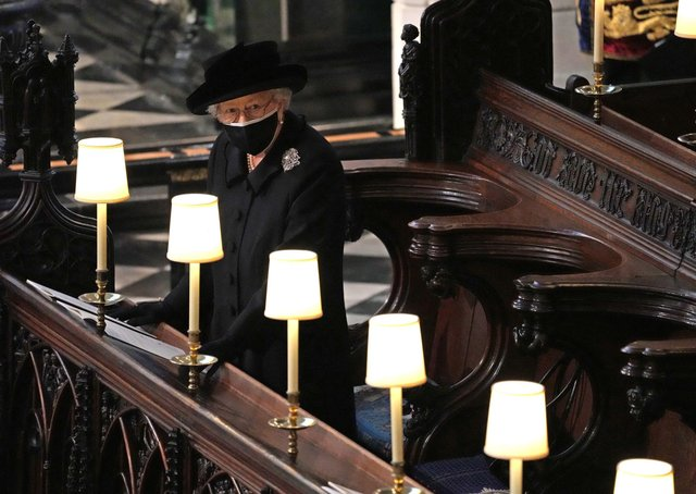 A heartbreaking photo of the Queen as she watches pallbearers carry Prince Philip's coffin through St George's Chapel during his funeral.