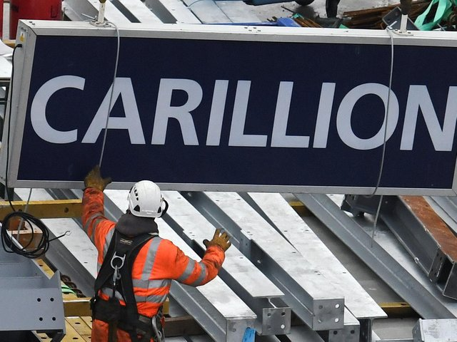 A worker guides down a sign showing the name of liquidated British construction and outsourcing group Carillion after it was taken down off a construction crane on a building site in the City of London on January 23, 2018. (Photo credit should read DANIEL SORABJI/AFP/Getty Images.