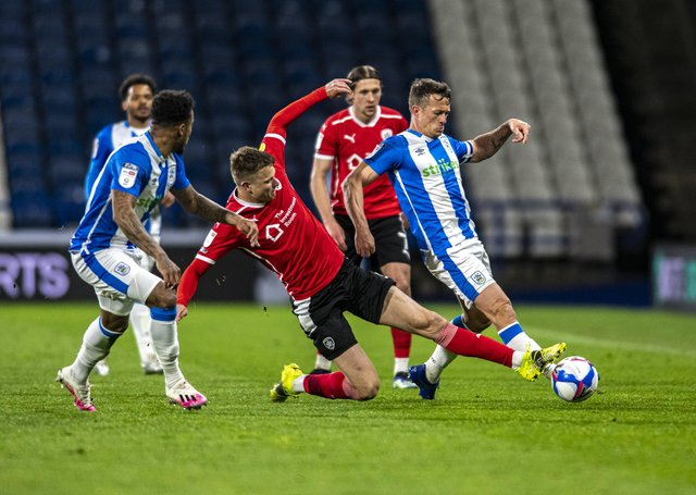 Huddersfield Town's Jonathan Hogg tackled by Tykes Masds Andersen.  (Picture: Tony Johnson)