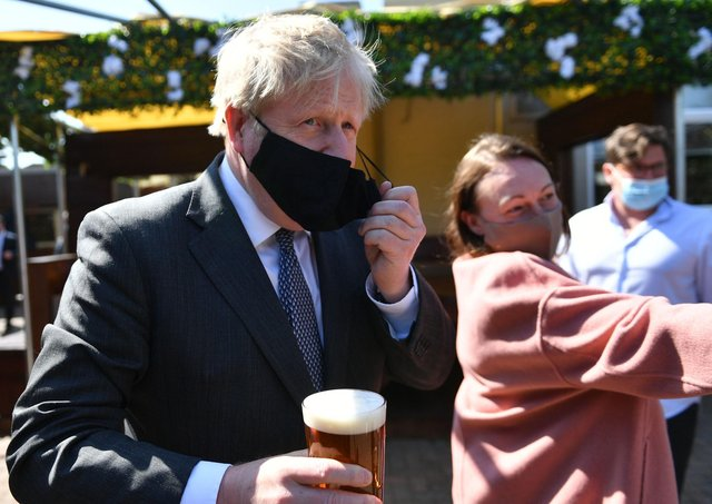 Prime Minister Boris Johnson removes his mask to enjoy a pint in the beer garden during a visit to The Mount Taven public house and restaurant in Wolverhampton, West Midlands, on the local election campaign trail. Picture: Jacob King/PA Wire