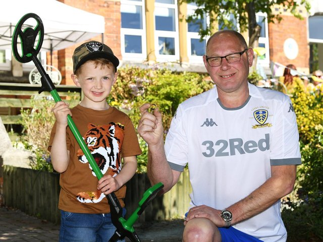 Bertie Lawson, five, with his metal detector and Rupert Denby with the wedding ring Bertie found.  Photo: Jonathan Gawthorpe
