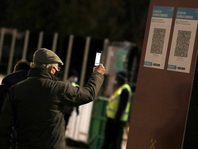 A West Ham United fans scans a track and trace code in December 2020. Picture: PA