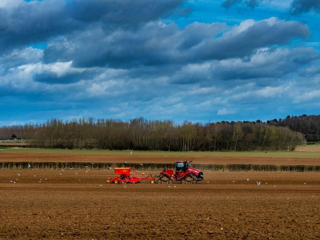 A farmer using an agriculture tractor sowing seeds on prepare land near Hazlewood Castle, Tadcaster. Picture: James Hardisty.