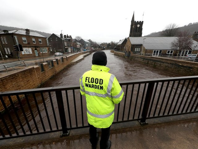 A flood warden looks at the water levels of the River Calder in Mytholmroyd in the Upper Calder Valley in West Yorkshire. Photo: PA