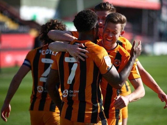 CELEBRATIONS: Hull City's players lap up Mallik Wilks's winning penalty at Lincoln.