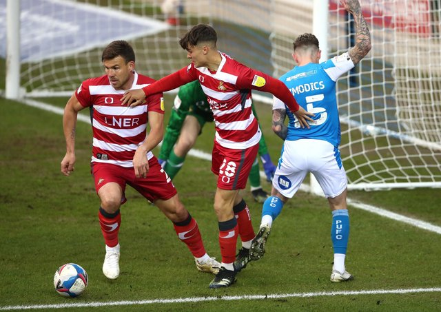 Peterborough United's Sammie Szmodics (right) and Doncaster Rovers' Branden Horton (centre) and Andy Butler all battle for the ball. Picture: PA