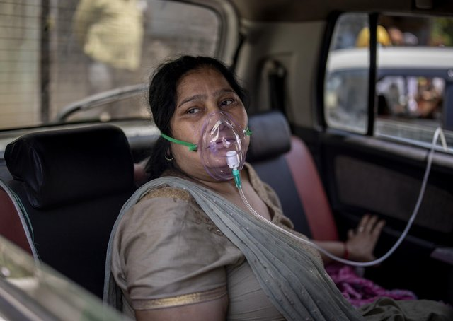 A COVID-19 patient sits inside a car and breathes with the help of oxygen provided by a Gurdwara, a Sikh house of worship, in New Delhi, India.