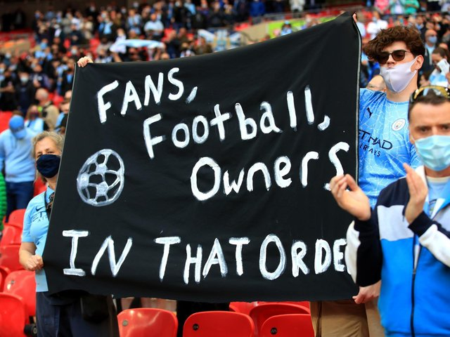 Fans hold up a banner protesting against the European Super League ahead of the Carabao Cup Final at Wembley Stadium, London.