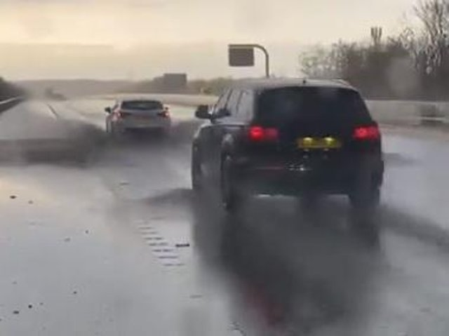 The video shows cars driving through standing water on the M62