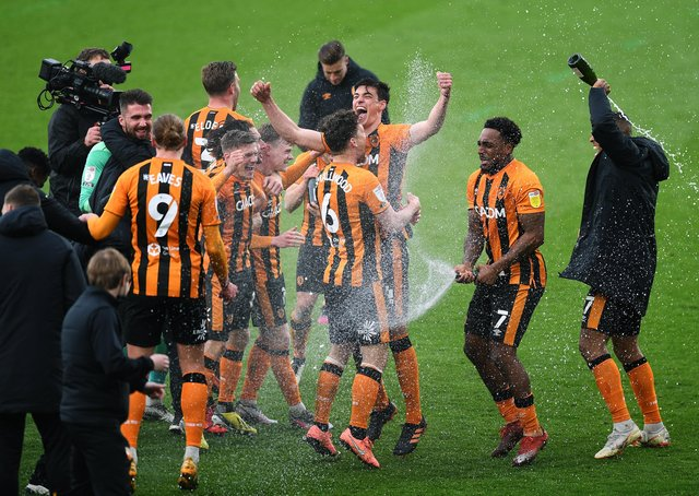 Let us spray: Hull City  forward Mallik Wilks, above right, sprays his team-mates with champagne after helping the Tigers to the League 1 title. Picture: Jonathan Gawthorpe