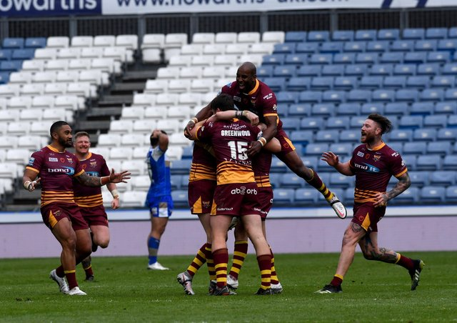 Huddersfield Giants' Lee Gaskell is mobbed by his team-mates after scoring a late, winning drop goal to sink Leeds Rhinos. Picture: Simon Hulme