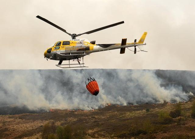 A helicopter drops water, taken from a nearby reservoir, onto the flames after a resurgence of the moor fire on Marsden Moor, near Huddersfield last week.