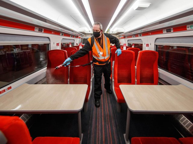 Library image of a cleaner using a fogging machine to clean a train carriage during the night
