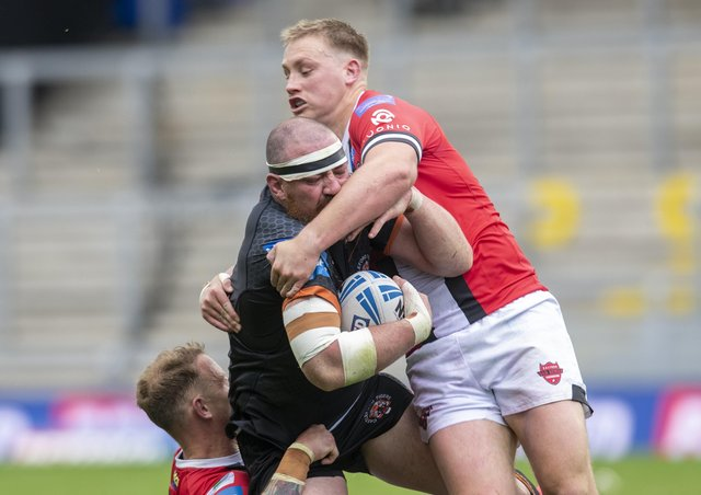 Castleford's Grant Millington is tackled by Salford's James Greenwood and Kevin Brown. Picture: Tony Johnson