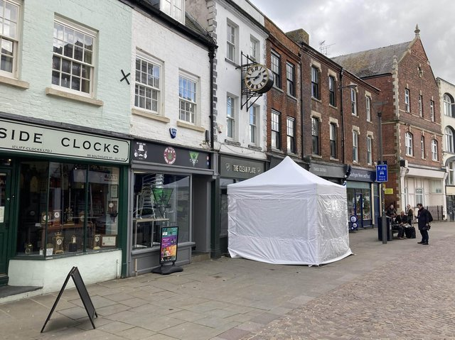 A police tent outside The Clean Plate cafe in Southgate Street, Gloucester, on Tuesday (May 11).