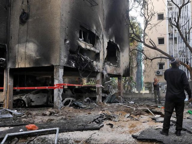 Israeli men check the damages after a rocket attack from the Hamas-controlled Gaza Strip, in the central Israeli city of Petah Tikva