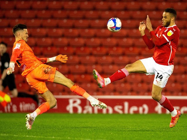 CHALLENGE: Barnsley's Carlton Morris competes for the ball with Freddie Woodman