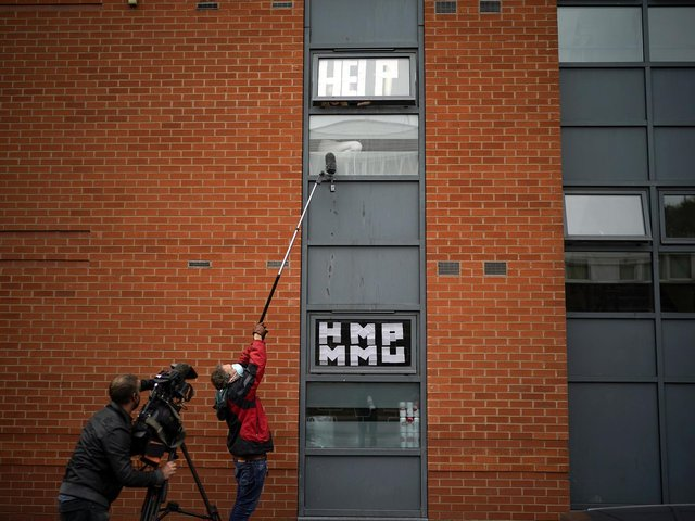 Pictured isolating students peer out of their accommodation window as they are interviewed by a television crew last year  in Manchester. The previous two academic years have been disrupted - with many students having to spend time isolating and months off campus. Photo credit: Christopher Furlong/Getty Images.
