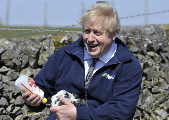 Boris Johnson during a recent farm visit as his commitment towards farmers comes under scrutiny.