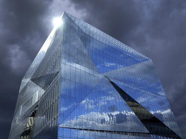 """Dark clouds are seen as the sun is reflected in the glass surface of the """"Cube Berlin"""" office building. PIC: PA"""