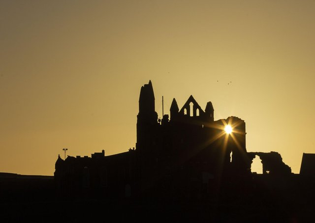 The sun rises behind Whitby Abbey as the town welcomes back visitors.