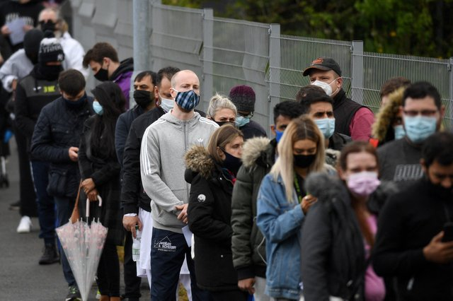 Members of the public queue to receive a Covid-19 vaccine at a temporary vaccination centre at the Essa academy in Bolton on May 17, 2021. (Photo by OLI SCARFF/AFP via Getty Images)