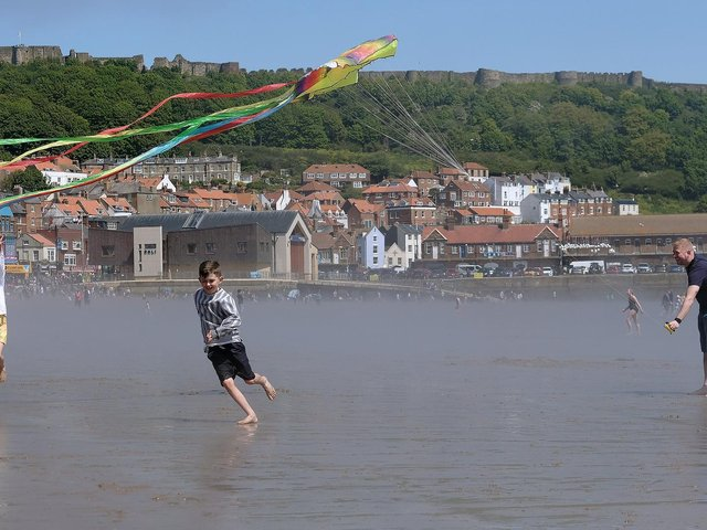 Children fly kites on the beach against Scarborough's iconic backdrop.