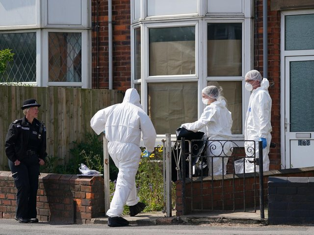 Police forensic officers work at the scene in High Holme Road, Louth, Lincolnshire, following the death of a woman and child on Monday. An urgent appeal has been issued by police to find Daniel Boulton, 29, in connection with the incident.