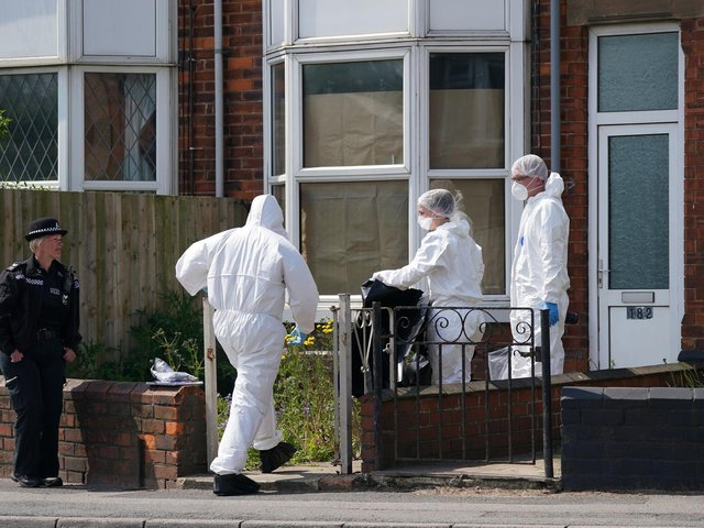 Police forensic officers work at the scene in High Holme Road, Louth, Lincolnshire, following the death of a woman and child on Monday