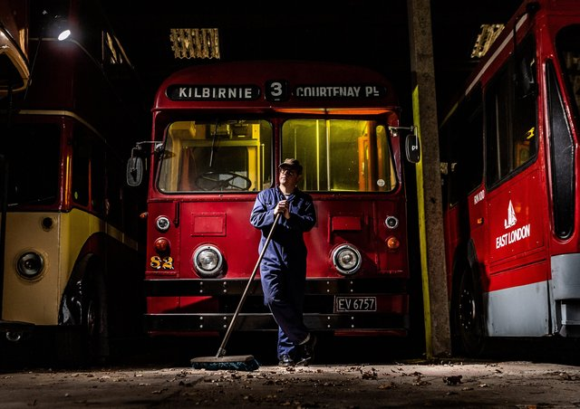Volunteer Ian Brown, takes time out from sweeping in the holding shed and rests against a Wellington TB 82 Trolleybus from New Zealand.