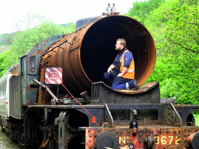 Apprentice Mark Readman checking out the boiler on the rusting Dame Vera Lynn  parked up in a siding near the sheds at Grosmont on the North York Moors Railway