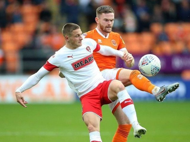 Defender Ollie Turton, in background, tussles for the ball with Rotherham United's Ben Wiles in the Millers' game at Blackpool in 2019.