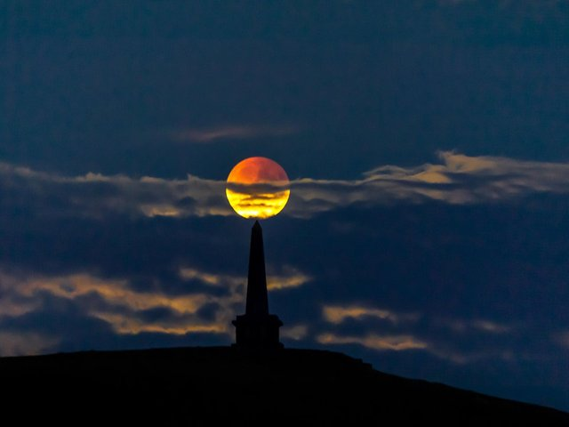 A partial lunar eclipse rising over Stoodley Pike, Todmorden in 2019