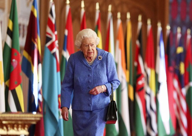 The Queen walking past Commonwealth flags in Windsor Castle.