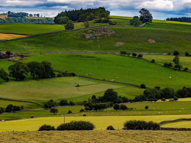 A farmer slowly makes his way back and forth cutting the grass in a field near Marrick, Richmondshire, North Yorkshire