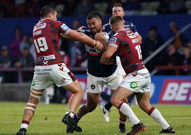 On a charge: Wakefield Trinity's David Fifita drives at Wigan Warriors' Liam Byrne and Eddie Battye.