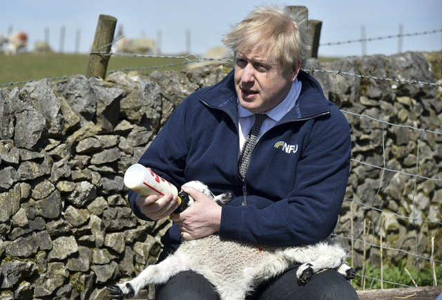 Prime Minister Boris Johnson feeds a lamb during a visit to the Moor Farm in Stoney Middleton, north Derbyshire, but will his post-Brexit trade deals be good for agriculture?