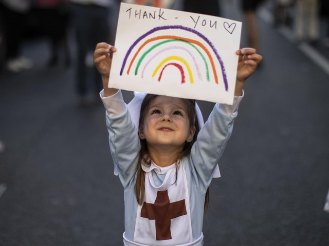 """Maria Sole, four, dressed in a small nurses outfit holds up a rainbow drawing with the words 'Thank You' on it as NHS staff and members of the public take part in the weekly """"Clap for Our Carers"""" event at Chelsea & Westminster Hospital on May 28, 2020 in London. Photo by Dan Kitwood/Getty Images."""
