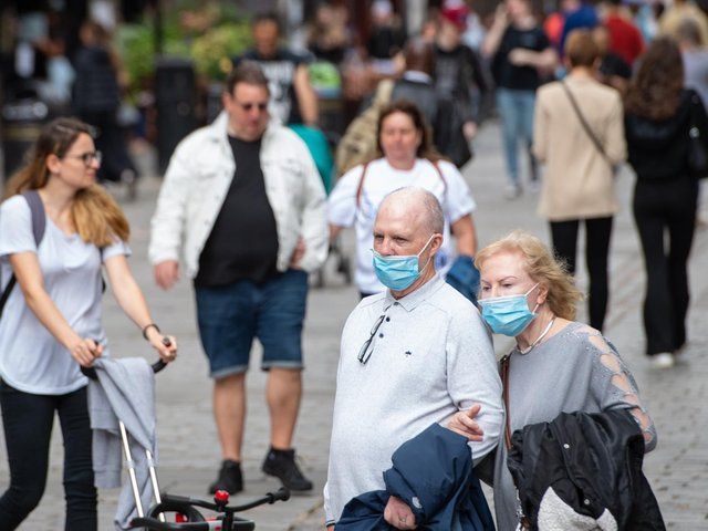 People wearing face masks watch a street entertainer in Covent Garden, London