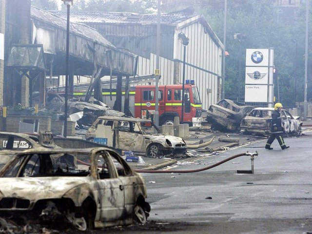 A firefighter outside a burned out BMW showroom in Bradford Sunday July 8 2001, after last night's violence in the city which was sparked by an Anti Nazi League demonstration against the National Front. Picture: PA