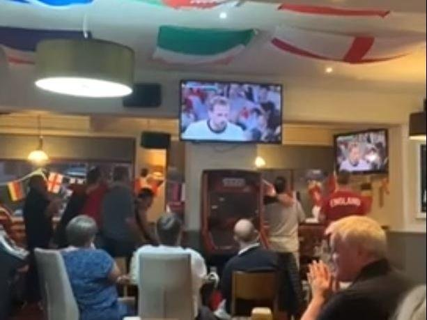 Englad fans watch in trepidation as Harry Kane steps up to take the penalty...
