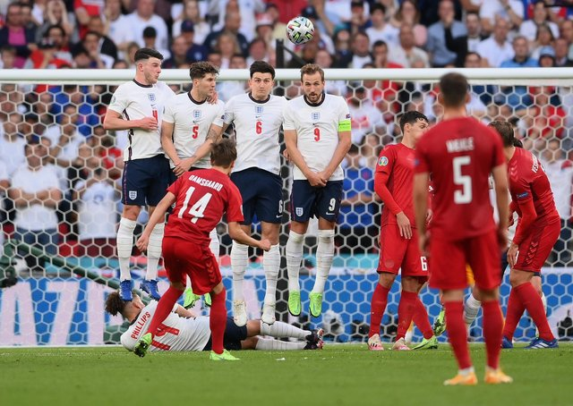 Mikkel Damsgaard of Denmark scores despite the close attention of England's wall. (Photo by Laurence Griffiths/Getty Images)