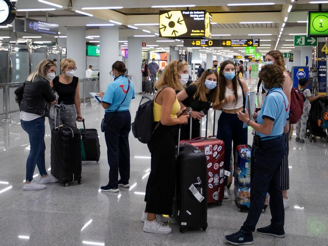 Representatives of tour operator TUI provide information to British tourists at the airport in Palma de Mallorca on July 27, 2020. (Photo by JAIME REINA/AFP via Getty Images)