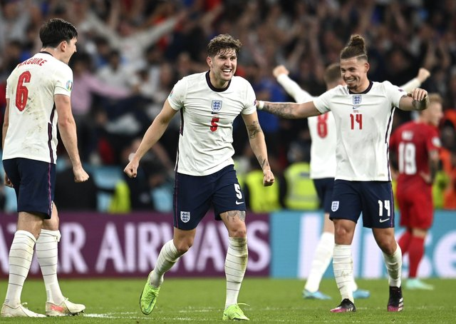 England's John Stones, center, Harry Maguire, left and Kalvin Phillips celebrate after beating Denmark in Wednesday night's semi-final. Picture: Andy Rain/AP