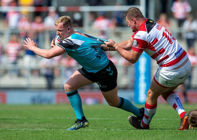 Jordan Johnstone is held back by Leigh's Ben Hellewell.  Picture Bruce Rollinson