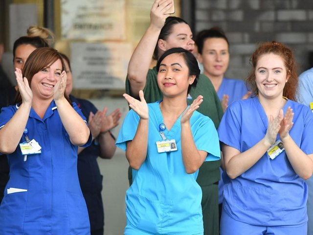 """NHS workers participate in a national """"clap for carers"""" event. Photo by Paul Ellis/AFP via Getty Images."""