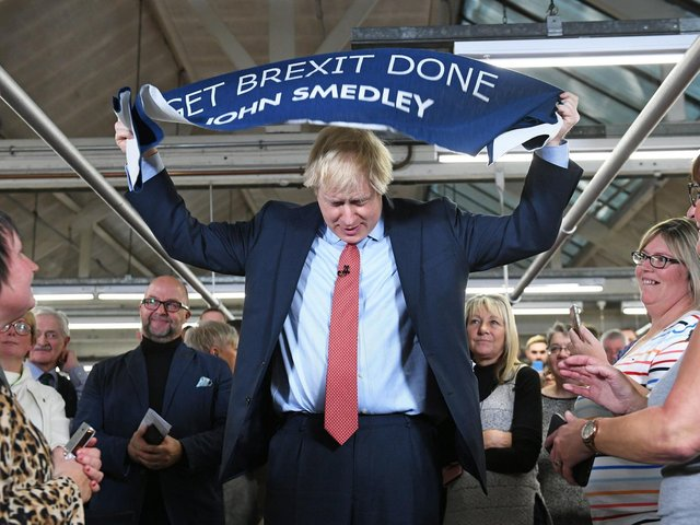Prime Minister Boris Johnson holds up a banner with the words 'Get Brexit Done' during a visit to the John Smedley Mill, while election campaigning in Matlock, Derbyshire. Picture: Stefan Rousseau/PA Wire
