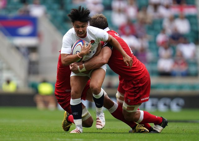 England's Marcus Smith (centre) tackled by Canada's Lucas Rumball (left) and Reegan O'Gorman during the Summer Series match at Twickenham Stadium, London. Picture date: Saturday July 10, 2021. PA Photo.Harlequins and England fly-half Marcus Smith has been called up by the British and Irish Lions as injury cover for Finn Russell, the Lions have announced. See PA story RUGBYU Lions. Photo credit should read: Andrew Matthews/PA Wire.  RESTRICTIONS: Use subject to restrictions. Editorial use only, no commercial use without prior consent from rights holder.