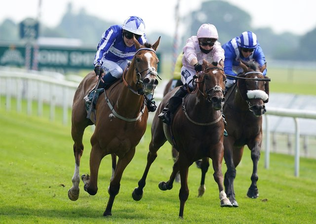 Johnny Drama and Joshua Bryan (left) coming home to win the John Smith's Cup Handicap at York on Saturday. Picture: Martin Rickett/PA