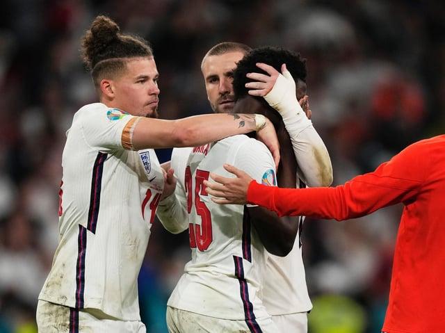 England players comfort Bukayo Saka at Wembley. Pic: Getty